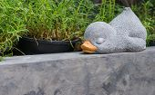 A sleeping duck made from cement for decoration in the garden poster