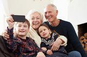 Grandparents And Grandchildren Sitting On Sofa Taking Selfie poster