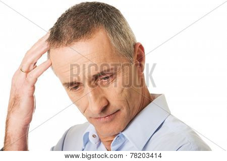 Portrait of confused man scratching his head.