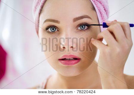 Close up of young beautiful  woman applying mascara