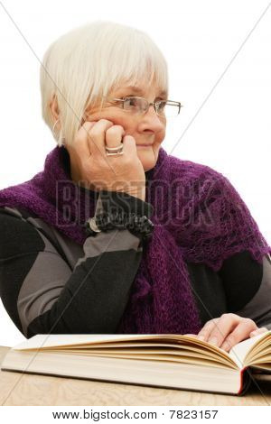 Relaxed Old Woman Looking Away While Reading A Book