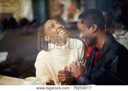 Laughing young couple in cafe having a great time together view through cafe window