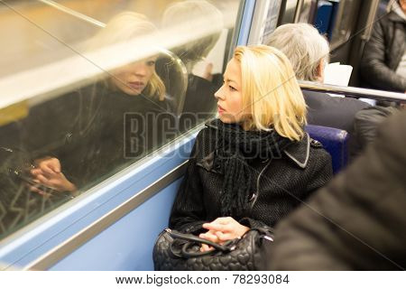 Woman looking out metro's window.
