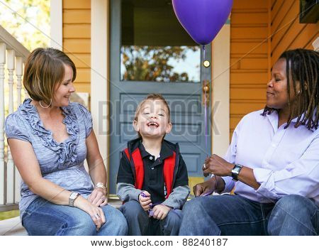 a cute diverse family sitting on a porch