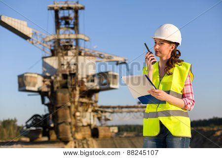 female worker talking on a radio on a background of career Stacker