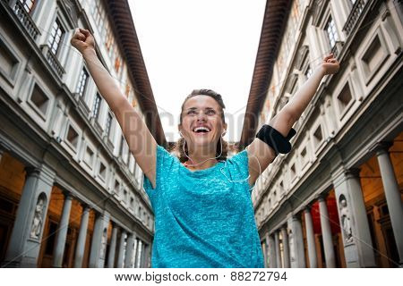 Happy fitness woman rejoicing near uffizi gallery in florence italy poster