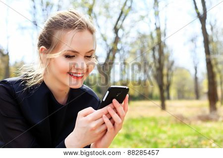 Woman With Unkempt Hair Looking Into Smartphone Smiling