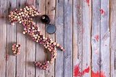Artistic conceptual map of Italy Sardinia and Sicily made of old red and white wine bottle corks on an old rustic wooden table with a glass and bottle of red wine alongside poster