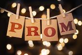 The word PROM printed on clothespin clipped cards in front of defocused glowing lights. poster