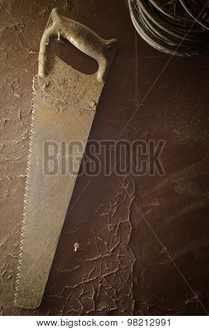 Old rusty saw on the dusty peeling wall. poster
