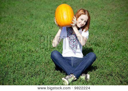 Young Women Sitting At Green Grass And Keeping Pumpkin.