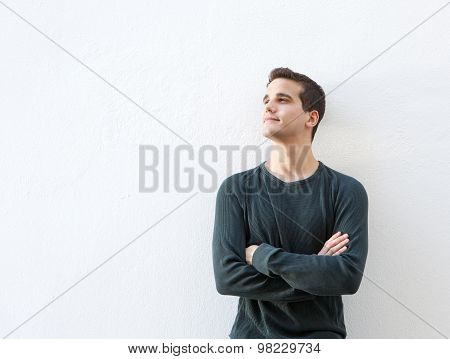 Young Man Standing Against White Background With Arms Folded