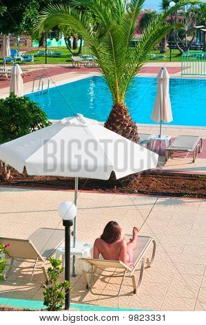 One Beautiful Woman Under Parasol Is Tained Near Water Pool