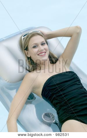 Attractive Young Blond Girl Relaxing In Swimming Pool