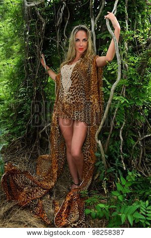 Young woman in luxury animal print dress among the jungle