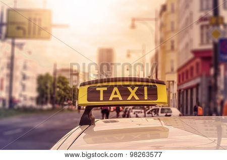 Taxi sign on top of a german cab in the evening sun, intentional selective focus