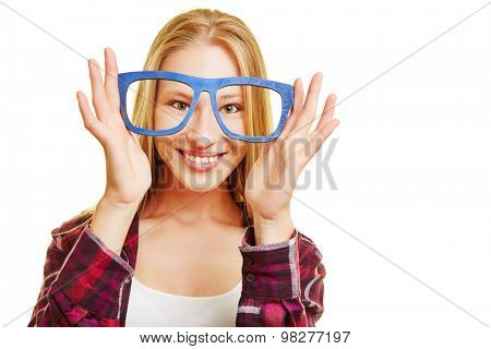 Young blonde woman holding fake nerd glasses in front of her eyes
