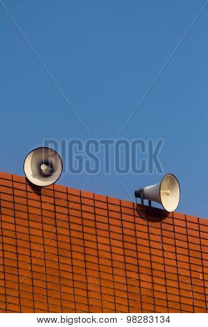 Loudspeakers On Builing And Blue Sky Background