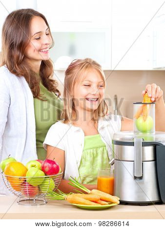 Happy Family making fresh apple and carrot juice. Smiling Mother and her daughter Girl drinking fresh carrot and apple juice. Juice Extractor. Healthy eating concept, vitamins.