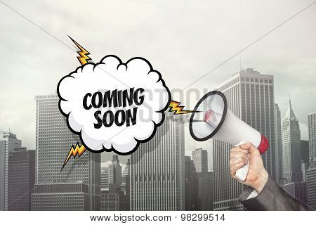 Coming soon text on speech bubble and businessman hand holding megaphone