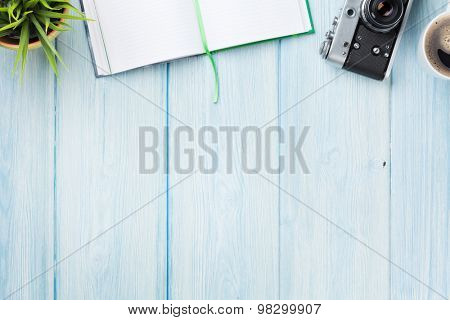 Office desk table with notepad, camera, coffee and flower. Top view with copy space