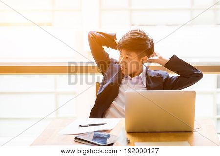 Asian short black hair business woman sit in front of laptop with relax positionand lazy position.