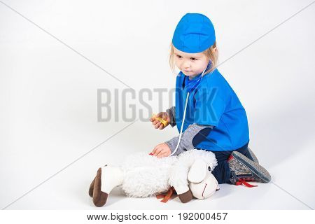 vet kid or small boy in blue uniform playing doctor with toy animal of donkey in medical hospital isolated on white background medicine and healthcare copy space