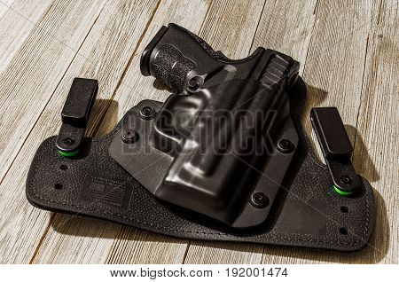 Black 9mm handgun on wood table in a holster