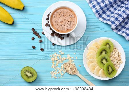 Breakfast with oatmeal porridge, coffee cup and fruits on blue wooden background. Oatmeal with kiwi and banana. Healthy breakfast concept. Top view