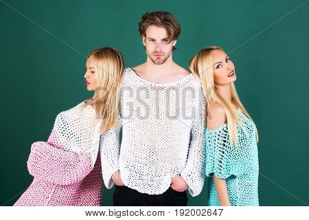 women or cute girls fashionable models with long blond hair makeup and caucasian man or macho posing in knitted stylish sweaters on green background. Fashion and beauty