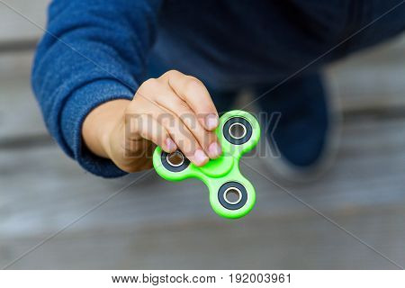 Child spinning a fidget spinner device. Top view