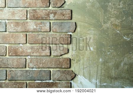 Terracotta stone brick tiles on grey grunge old cement wall surface on masonry background. Construction building materials and renovation