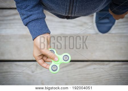 Child spinning a fidget spinner toy. Top view