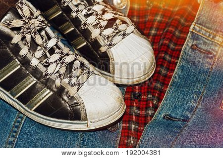 A pare of old worn sneakers standing on the lumberjack's shirt and retro styled denim jacket