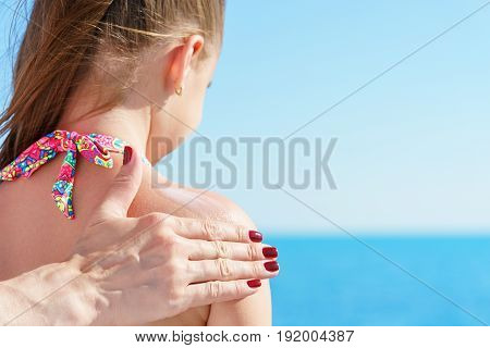 european mom is applying sun protector cream at shoulder of her young pretty daughter on the beach close to tropical turquoise sea under blue sky at sunny day.