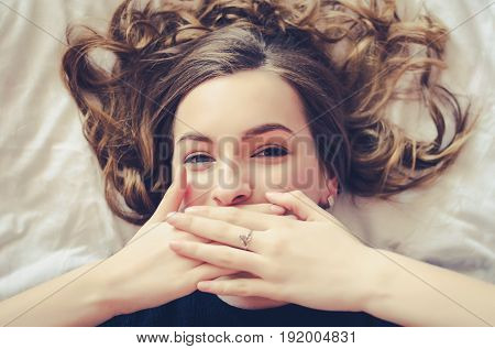 Laughing teen girl covering her mouth with her hands and looking at the camera. Beautiful young woman with curly fair hair lying on the bed on white sheet. Positive human emotion facial expression.