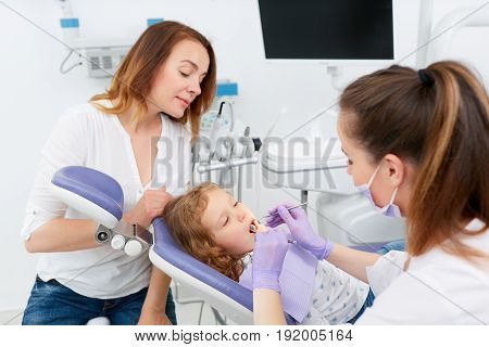 Medics in dentist cabinet using tools for examine and cure little adorable girl sitting in chair in a hospital. Little girl sitting in the dentists office