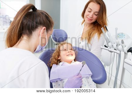 Female dentist in uniform with assistant showing a tool to little girl sitting in chair in a hospital. Dentist and child in cabinet. Dentist office.
