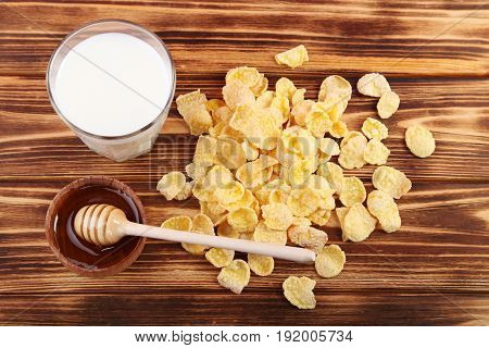 Cornflakes, Glass Of Milk And Bowl Of Honey On Wooden Table