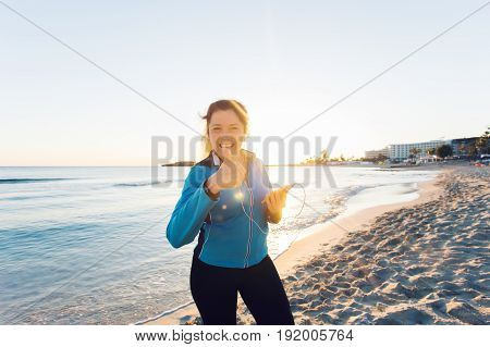 Concept of sport, fitness, healthy lifestyle and running - Motivated sporty woman doing thumbs up success gesture after outdoors workout at the beach.