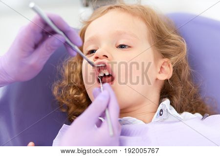 Hands of unrecognizable pediatric dentist holding lip up and making examination of cute little girl in chair in a hospital. Dentist and child in cabinet. Dentist office.
