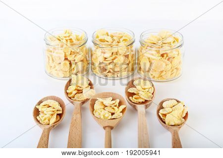 Cornflakes In Glass Jar And Wooden Spoons Isolated On White
