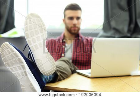 Portrait of a very relaxed young designer leaning back on his desk and putting his feet up his desk at the office