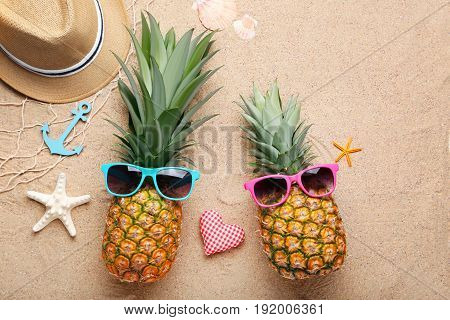 Ripe Pineapples With Sunglasses On Beach Sand