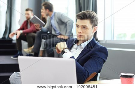 Young smart people are using gadgets while working hard in the modern office. Young man working on his laptop