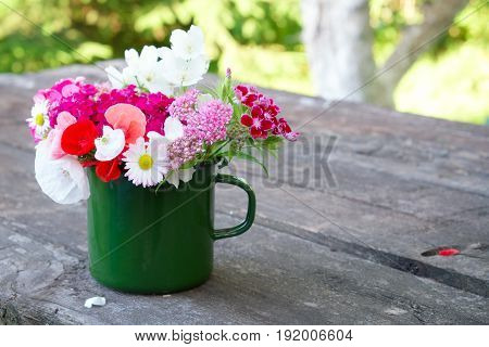 Bouquet of garden flowers in green enameled mug on old wooden table outdoors.