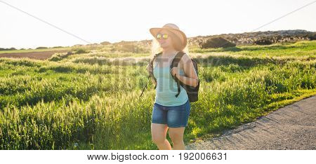 Traveler woman with map on nature. Concept of travel, hitch-hiking and vacation