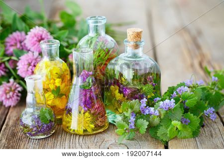 Bottles and vials of tincture or infusion of healing herbs medicinal herbs on rustic wooden board. Herbal medicine concept.