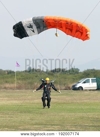 Male Skydiver Making Safe Landing Landing On Grass With Open Bright Colourful Parachute.