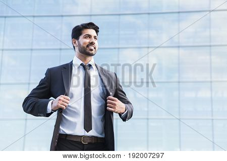 Arabic serious smiling happy successful positive businessman or worker in black suit with beard standing in front of an office glass building and holding his jacket with his hands.